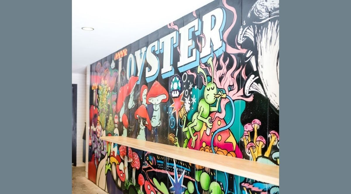 """Plant-based eatery Oyster Oyster's debut, which took place in August had been relegated to takeout, but a new onsite, outdoor experience, known as """"2-Hour Parking"""" has arrived. A covered outdoor space, which was originally meant to be a loading dock for a supermarket is now the home of psychedelic murals, pinball machines and a group dining experience like no other."""